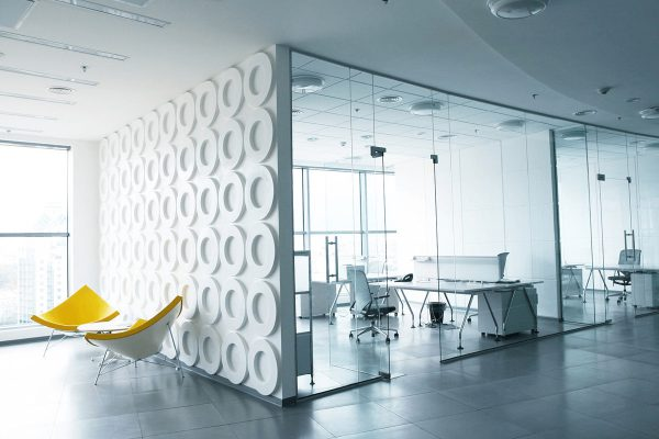 Modern office design with glass walled meeting rooms and two yellow chairs in foreground
