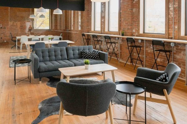 Exposed brick modern office space with grey sofa in coffee break area
