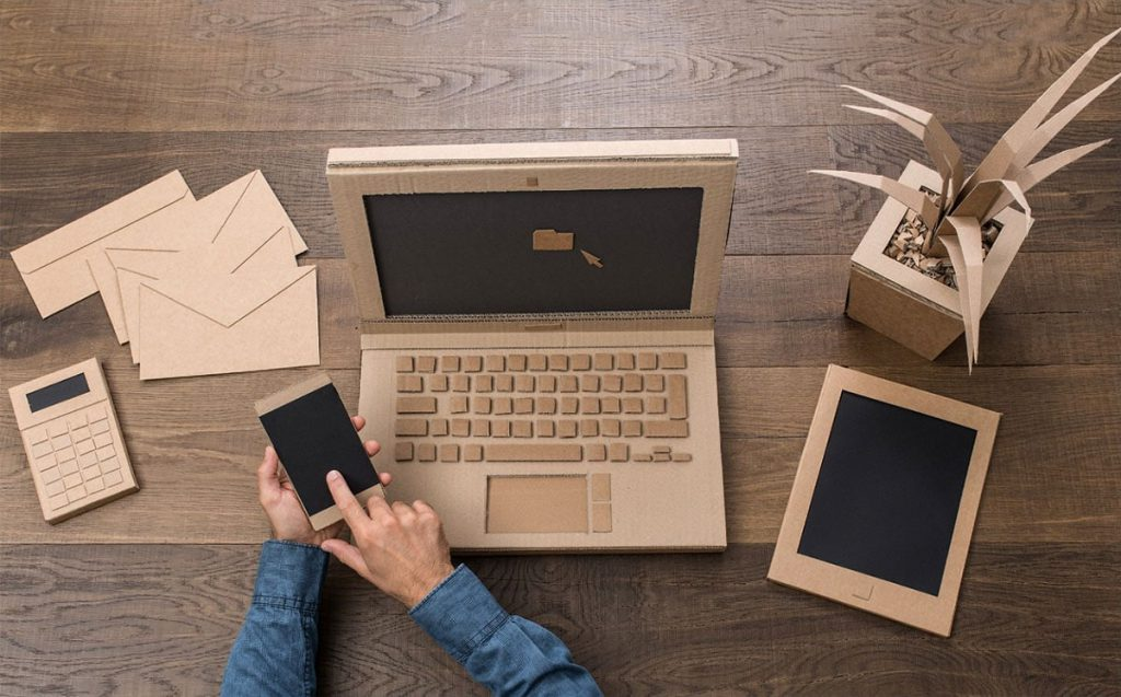 Office desk with computer, tablet, calculator, and plant made out of cardboard