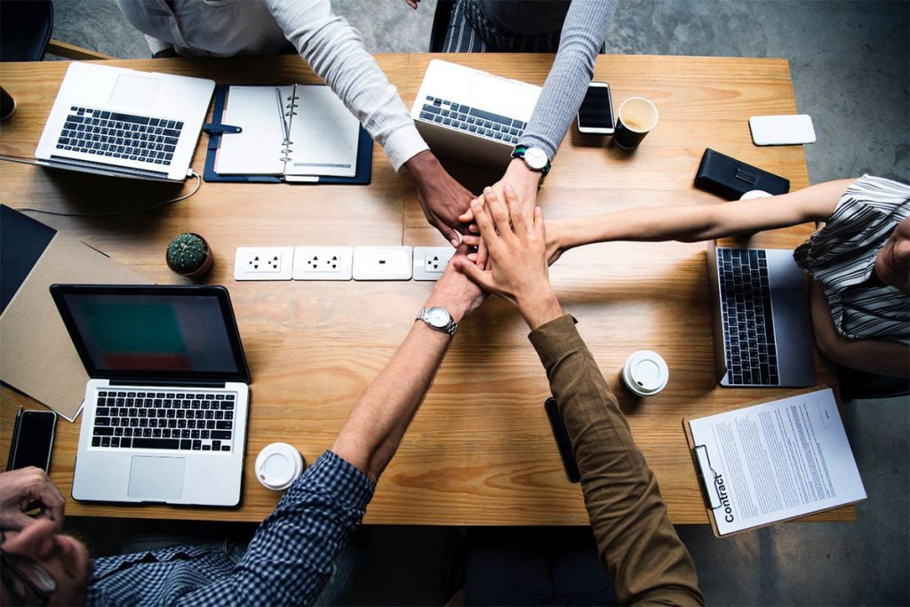 An image from above of five business people with their hands in the centre of a meeting table.