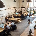 A shot of several businesspeople at work in an open plan office, through the strings of fairylights.