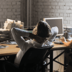 Worker meditates at his office desk