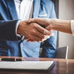 Real estate agent and customers shaking hands together celebrating finished contract