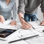 Two interior designers examine office design schematics
