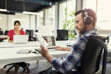 Serious man working on laptop while listening to music in open space business company
