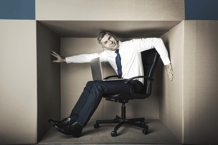 Businessman in small office box working on laptop, he needs more space