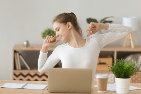 A young relaxed woman enjoys distance online work at home workplace